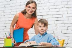 Lehrer und Schüler, die zusammen Aufgabe tun lizenzfreie stockbilder