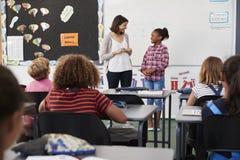 Lehrer und Schüler stehen an der Front der grundlegenden Schulklasse lizenzfreie stockfotos