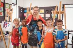 Lehrer und Schulkind, die zusammen in der Zeichenklasse stehen Stockfotografie
