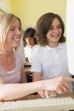 Lehrer und Schulmädchen, die auf einem Computer studieren Stockfoto