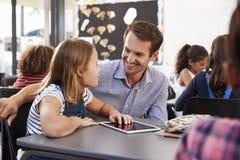 Lehrer und Schulmädchen, welches die Tablette betrachtet einander verwendet Lizenzfreies Stockfoto