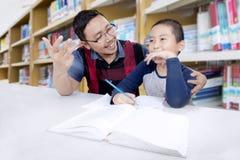 Lehrer und Student, die Mathe in der Bibliothek studieren stockbild