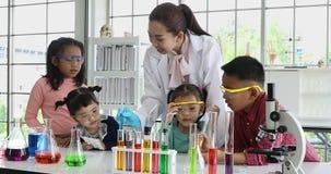 Lehrer und Studenten betrachten Experiment auf Tabelle stock footage