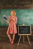 Lehrerlesebuch im Klassenzimmer Hübsche Frau ist zurück zu Schul- und Lesebuch an der Tafel Entzückend und Genie stockbild