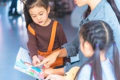 Lehrerlesegeschichtenbuch zu den Kindergartenstudenten lizenzfreie stockfotos
