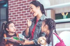 Lehrerlesegeschichtenbuch zu den Kindergartenstudenten greifen oben ab lizenzfreies stockbild