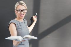 Lehrerschreiben mit Kreide auf Tafel und Holding ein offenes Buch Stockbild