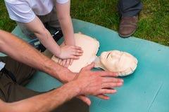 Lehrershow, wie man der ersten Hilfe Herzkompressionen unter Verwendung der Attrappe während der Kinder gibt, die draußen ausbild lizenzfreies stockbild