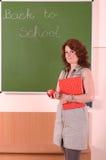 Lehrerstand mit Buch und Apfel in ihrer Hand lizenzfreies stockbild