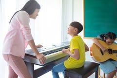 Lehrerunterrichtskinder, die Musik-Instrumente spielen stockbilder