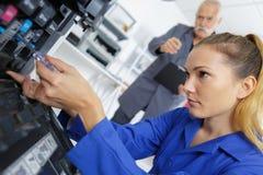 Lehrling, der eine Maschine repariert lizenzfreies stockfoto