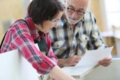 Lehrling der jungen Frau in der Zimmerei mit älterem Handwerker stockfotografie