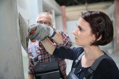 Lehrling der jungen Frau in plastery mit Professor stockbild