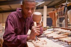 Lehrling, der Meißel verwendet, um Holz in der Werkstatt zu schnitzen lizenzfreie stockfotografie