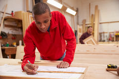 Lehrling, der mit Plänen in der Zimmerei-Werkstatt arbeitet lizenzfreie stockfotos