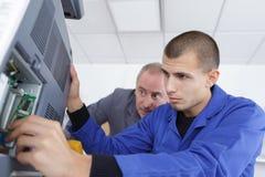 Lehrling, der versucht, Computer zu reparieren stockfotografie