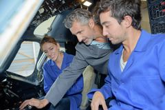 2 Lehrlinge und aero Mechaniker des Lehrers im Flugzeugcockpit Stockfoto