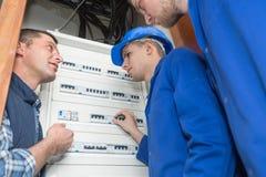 Lehrlingselektriker, die durch fusebox lernen lizenzfreies stockfoto