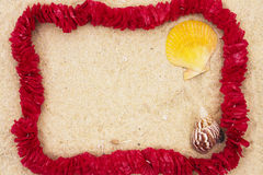 Lei on beach. Lei on sand with shells with copy space in center Royalty Free Stock Images