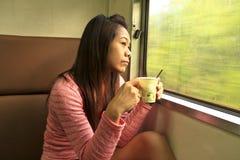 Lei caffè bevente nel treno Immagine Stock