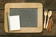 Leibord en houten lepel en leeg de notaboek van de aardetoon met kaneel Royalty-vrije Stock Afbeelding