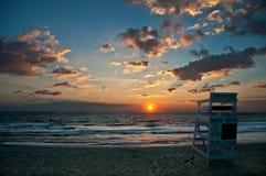Leibwächterstuhl auf Strand bei Sonnenaufgang Stockfoto