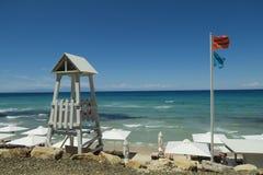 Leibwächterturm mit Leibwächterflagge auf einem griechischen Strand Lizenzfreie Stockbilder