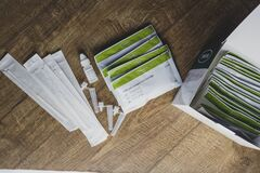 Covid immunisation cards issued after vaccination, next to Lateral Flow home testing kits.