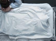 Leiche in einem Krankenhausbett bedeckt mit einem Kopf und einer leidenden Frau Lizenzfreie Stockfotos
