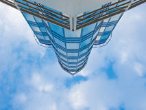 Leicht geschlagenes Oberteil eines modernen Gebäudes mit Glasfassade Stockfotografie