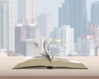 Leicht schlagend konkurrieren Seiten des offenen Buches auf hölzerner Tabelle mit Stadtgebäude lizenzfreie abbildung