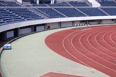 Leichtathletiklaufbahn und leere Sitze stockbild