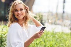 Leichte lächelnde kaukasische Frau mit dem Mobiltelefon, das im grünen Park stillsteht Stockfotografie