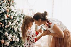 Leichte Mutter mit ihrer kleinen Tochter gekleidet im Pyjama nahe bei dem Baum des neuen Jahres im vollen des hellen gemütlichen lizenzfreie stockfotografie