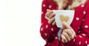 Leichte schöne Mädchenhände halten helles geschmackvolles süßes Weihnachtsherz-förmige Plätzchen mit einem Becher Tee lizenzfreies stockfoto