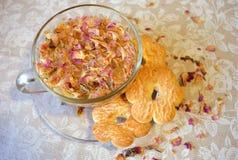 Leichte Zusammensetzung des Getränks der rosafarbenen Blumenblätter des Tees, der transparenten Tasse und Untertasse, der Plätzch Lizenzfreies Stockfoto