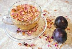 Leichte Zusammensetzung des Getränks der rosafarbenen Blumenblätter des Tees, der transparenten Tasse und Untertasse, der Pflaume Lizenzfreie Stockbilder