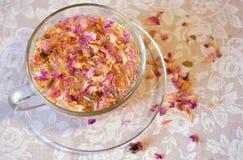 Leichte Zusammensetzung des Getränks der rosafarbenen Blumenblätter des Tees, der transparenten Tasse und Untertasse und der zers Lizenzfreie Stockfotos