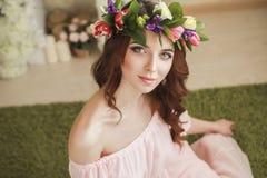 Leichter romantischer Auftritt des Mädchens mit einem Kranz von Rosen auf ihrem Kopf und einem rosa Kleid Frohe lustige Frühlings lizenzfreies stockfoto