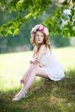 Leichtes romantisches Mädchen in einem Kranz von Pfingstrosen sitzt auf einer Wiese Stockfotografie