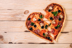 Leid formte Pizza mit Tomaten und Mozzarella für Valentinsgruß-Tag auf Weinleseschwarzhintergrund Lebensmittelkonzept von Stockbild