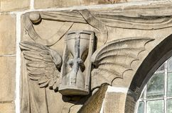 Time flies sculpture. Leiden, The Netherlands, April 25, 2018: detail in the facade of Hooglandse Kerk showing an hourglass with wingsto symbolize the phrase ` royalty free stock photo