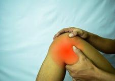 Leiden unter Gelenkschmerzen mit roter Stelle Hände auf Bein als Schmerzen von der Arthritis Arthroseknie-Krankheitskonzept stockbild