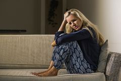 Leidende Krise der deprimierten und besorgten schönen Blondine und Angstkrisengefühl frustriert und Denken einsam am hom stockbild