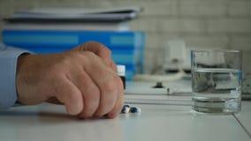 Leidender Geschäftsmann im Büro-Raum öffnen eine Empfänger und nehmen medizinische Pillen stock video