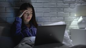 Leidenkopfschmerzen der jungen Frau, spät arbeitend im Schlafzimmer nachts, Workaholic stock video footage