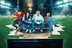 Leidenschaftliche Fans sitzen im dem Sofa und dem aufpassenden Fernsehen mitten in einem Fußballplatz Lizenzfreies Stockbild