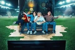 Leidenschaftliche Fans sitzen im dem Sofa und dem aufpassenden Fernsehen mitten in einem Fußballplatz Stockfotografie