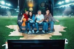 Leidenschaftliche Fans sitzen im dem Sofa und dem aufpassenden Fernsehen mitten in einem Fußballplatz Stockfoto