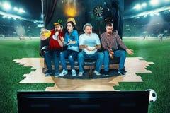 Leidenschaftliche Fans sitzen im dem Sofa und dem aufpassenden Fernsehen mitten in einem Fußballplatz Stockbilder